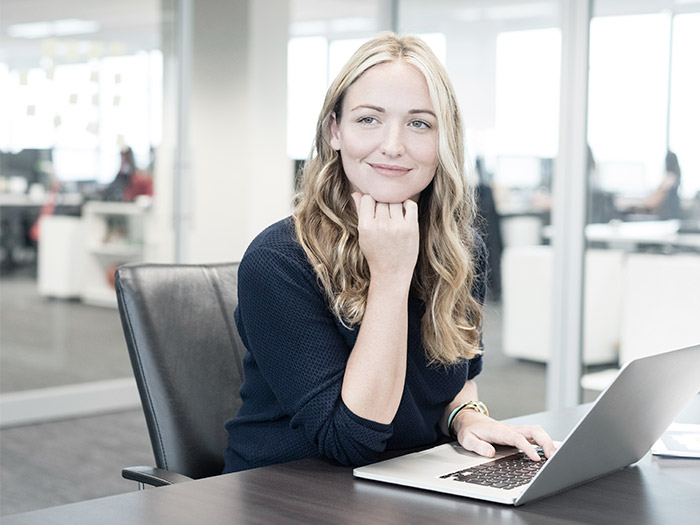 Smiling woman at laptop | Atradius