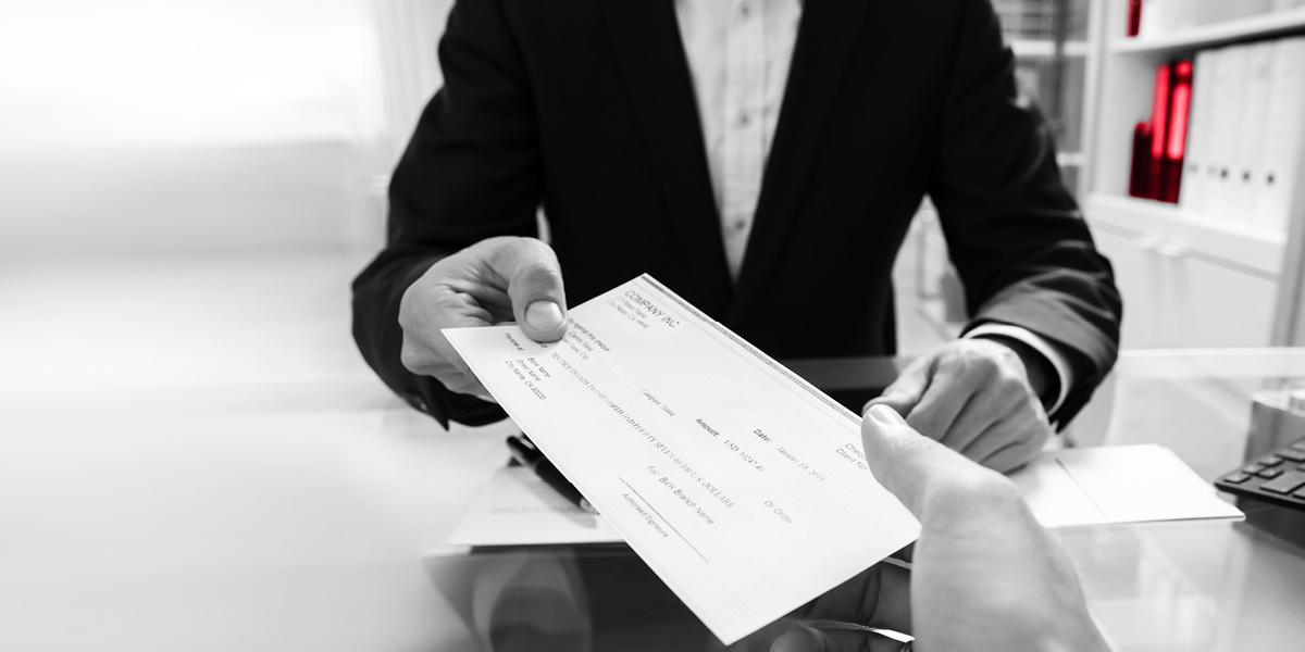 Man handing over a cheque | Atradius